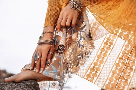 close up of woman hands with boho style accessories outdoors at sunset
