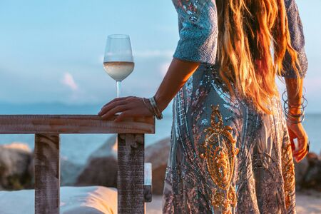 close up of beautiful l fashion model in elegant dress at sunset with glass of wine 免版税图像