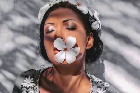 close up of beautiful young woman wearing wreath and holding frangipani flowers near face at white background Stock Photo
