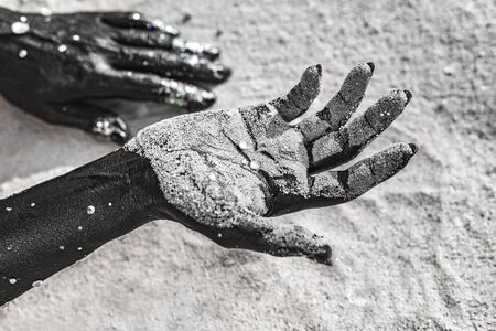 close up of woman hands painted black on sand. conceptual image