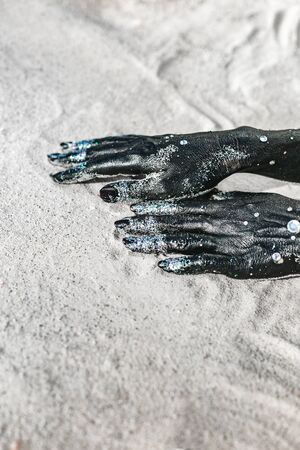 close up of woman hands painted black. moon and stars concept