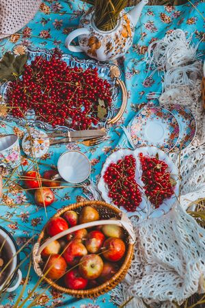 fresh fruits and berries in plates and wicker basket on tablecloth. top view Stock Photo