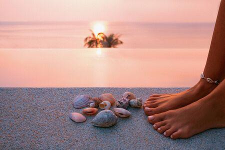 close up of woman hands and seashells at the pool at resort at sunset