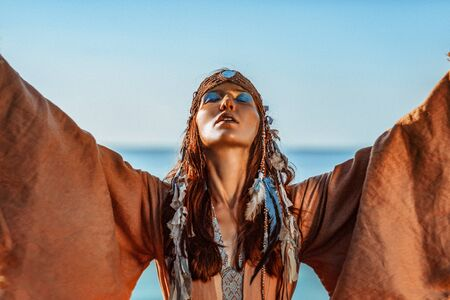 beautiful young woman in tribal costume outdoors portrait at sunset Foto de archivo