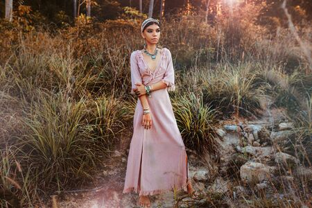 beautiful young fashionable woman in dress on the field at sunset