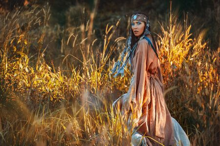Beautiful young stylish woman on the field at sunset. Oriental tribal princess Reklamní fotografie