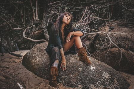 beautiful young stylish tribal style woman sitting on the rock outdoors Reklamní fotografie