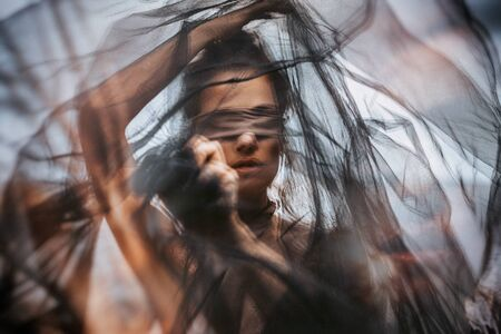 beautiful young woman covered with fabric and blindfolded. double exposure concept Standard-Bild