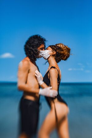 young couple hugging and kissing through the face masks on the beach