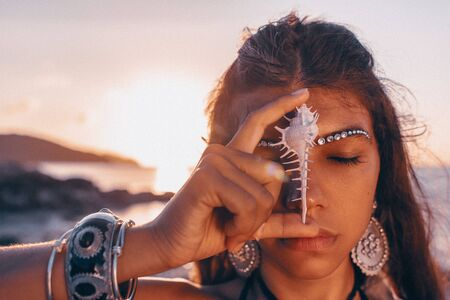 beautiful young tribal style woman holding sea shell at her face with eyes closed outdoors at sunset Standard-Bild