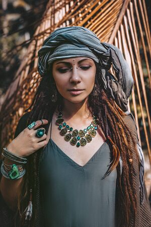 beautiful young stylish woman wearing turban with oriental accessories outdoors