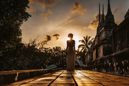 silhouette of young woman walking at ancient temple at sunset Standard-Bild