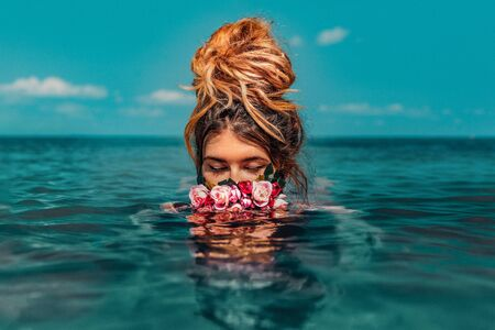 beautiful young woman swimming in sea with wreath conceptual fashion portrait  Standard-Bild