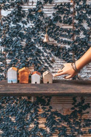 woman hand touching toy houses on wooden shelf. design decoration close up concept