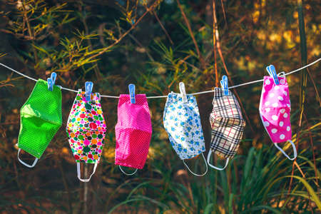 face masks with different style prints hang and dry on clothespins outdoors at sunset Reklamní fotografie