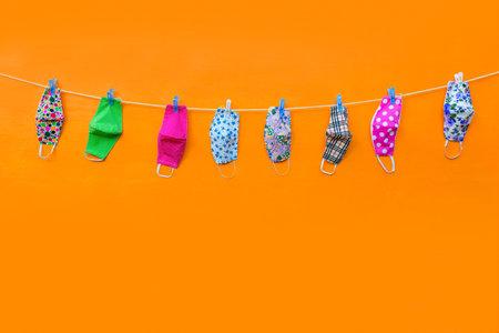 face masks hang and dry on clothespins at orange background Reklamní fotografie