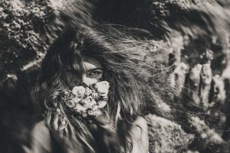beautiful young woman cover her face with flowers. black and white portrait. conceptual tilt shift effect. Reklamní fotografie