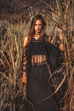 beautiful young stylish fashionable woman posing on the field at sunset Reklamní fotografie