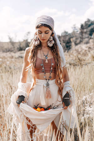 beautiful stylish young girl holding tangerines in the hem of her skirt on the field Reklamní fotografie