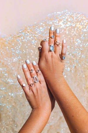beautiful young woman hand with may rings at sea shore background close up Reklamní fotografie