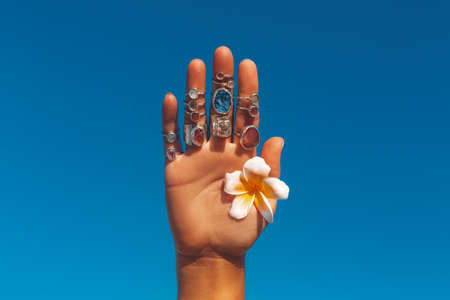 woman hand with many rings holding frangipani flower at blue sky background Reklamní fotografie