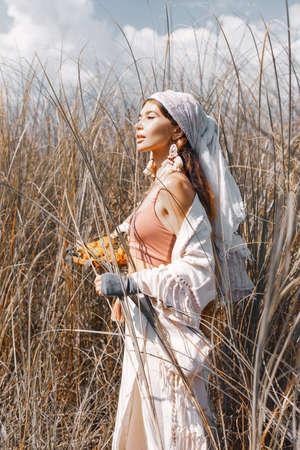 beautiful stylish young countryside woman on the field