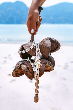 woman holding tropical branch with necklace made of seashells at sea shore background close up Reklamní fotografie