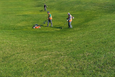 KHABAROVSK, RUSSIA, JUNE 6, 2012: Gardeners are cutting grass in a city park.