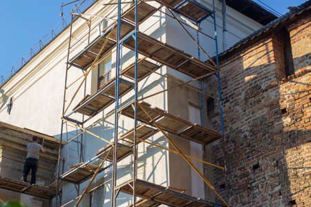 Worker on scaffolding at restoration work