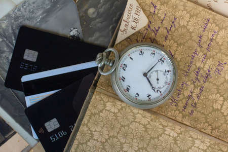 Antique items with bank cards. Pocket watch from the 19th century. Antique trade. Vintage background.