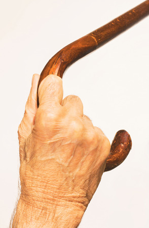 Elderly man hand with amputated finger leaning on walking stick. Stock Photo