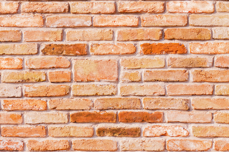 Wallpaper of a red antique brick wall with colored bricks looks like a happy face. Stock Photo