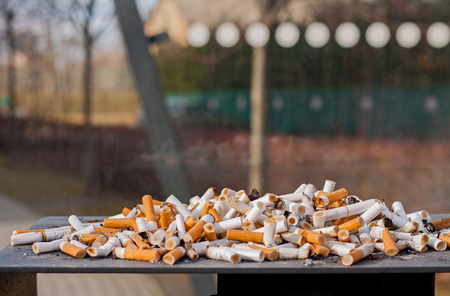 Cluster of cigarette butts gathered from smokers in an ashtray of a bus station.
