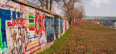 Colorful graffiti on stonewall dike near a bridge in Budapest.