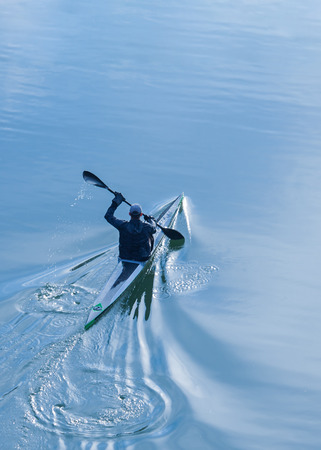 Sportsman rowing alone in a Kayak on Danube river.