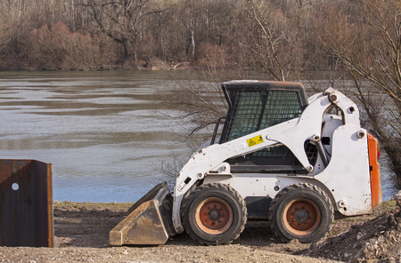 Earthmover on the protection dam under construction on river Danube