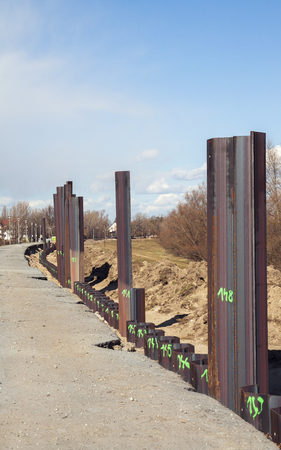 Steel pillar hitting in the ground to stabilize the flood protection dam Stockfoto