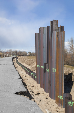 Row of steel pillar hitting in the ground to stabilizes the flood protection dam Stockfoto