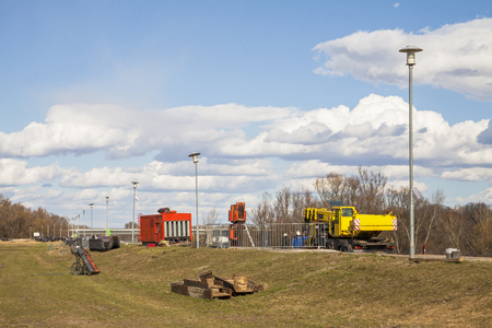 Flood protection dam under construction on river Danube with crane and genset. Banque d'images
