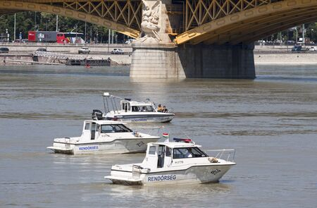 Budapest, Hungary – June 11, 2019; Police boat assure the area of the raising action of the sunken Hableany tour ship in Danube next to Margaret Bridge.