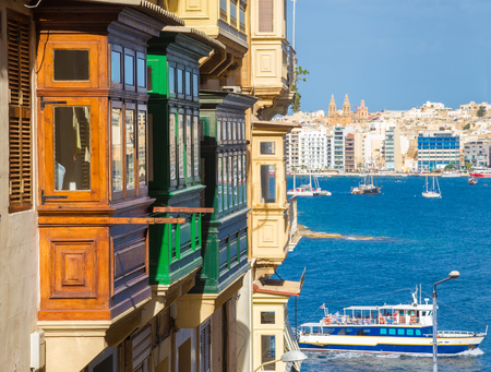 Traditional maltese brown and green balconies of Valletta and tourist ship with view of Malta