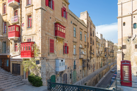 Streetview of Valletta with red balconies and phone booth, Malta