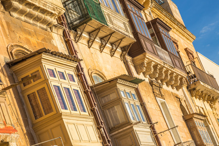 Typical ancient houses and balconies of Valletta at sunrise - Malta