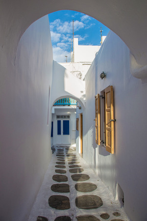 quaint: Mykonos streetview with arch and blue sky, Greece Stock Photo