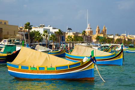 Marsaxlokk market with Luzzu colorful fishing boats, Malta