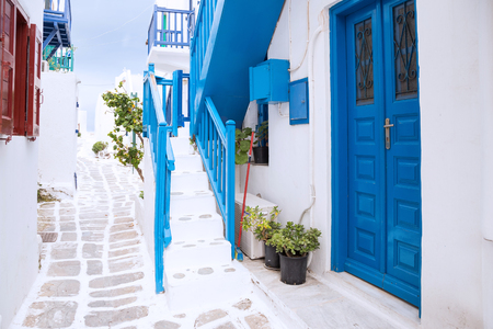 Streetview of Mykonos town with white street and blue door, Greece