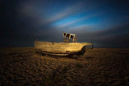 dungeness: Wrecked ship in sunset at Dungeness beach, England, UK Stock Photo
