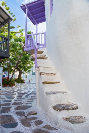 Mykonos street view with white stairs, trees and purple balcony, Greece