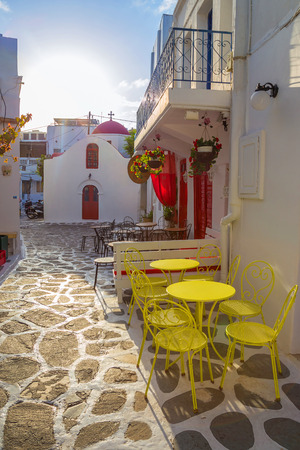 Mykonos streetview at sunrise with chapel and yellow chairs and tables, Greece Reklamní fotografie