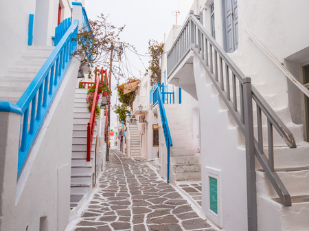 banisters: Mykonos town streetview with stairs and blue and grey and red banisters, Greece Stock Photo